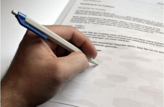 Bild einer Hand, die einen Stift hält und auf ein beschriebenes Blatt Papier unterschreibt
