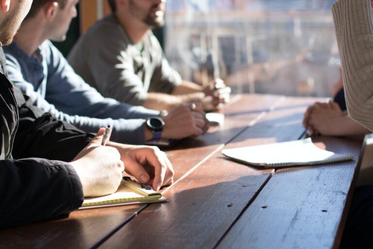 Menschen mit Stiften und Papier an einem Tisch